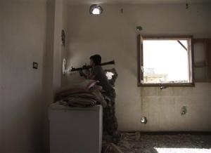 A member of the Free Syrian Army aims his RPG through a hole as he takes up a defensive position in Deir al-Zor