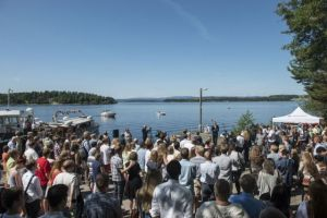 crowds gather by the shore to remember