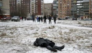 a woman lies dead as people pass by in Kramatorsk